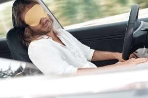 Man sleeping while autopilot is driving the car