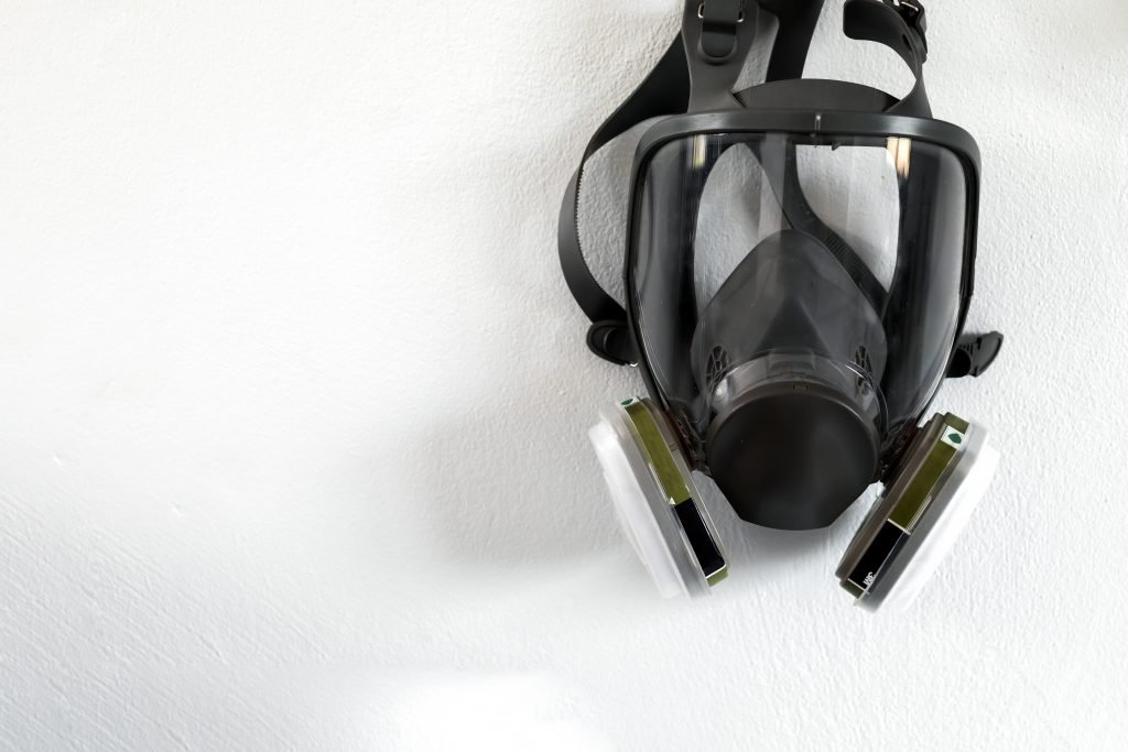 stop PM2.5 banner. closeup respirator mask industrial cartridge filter anti-dust safety chemical on white brick wall with soft-focus and over light in the background