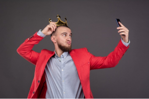 Man in red suitcoat with crown taking a selfie